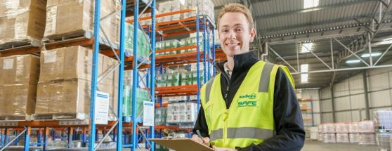 Sadleirs employee standing in front stacked packaging in warehouse