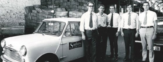 five past employees standing in a row at the side of an old Sadleirs car