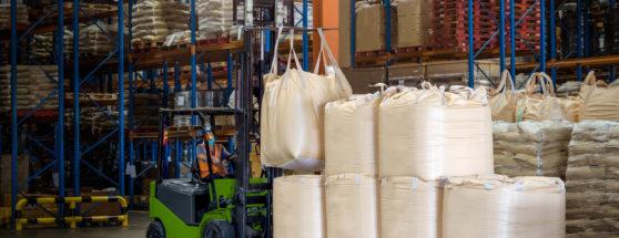 Forklift handling bulk bags in warehouse